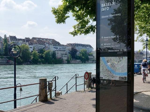 Blick auf eine Stele. Man blickt vom Kleinbasler Rheinufer aufs Grossbasel.