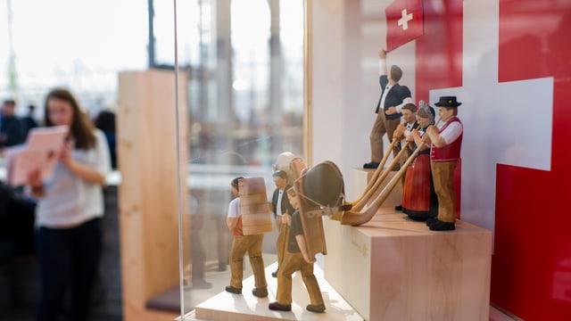 figurettas cun costums tradiziunals svizzers e tibas avant la bandiera svizra