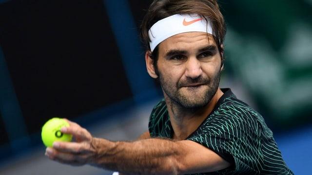 Roger Federer wirft einen Ball.