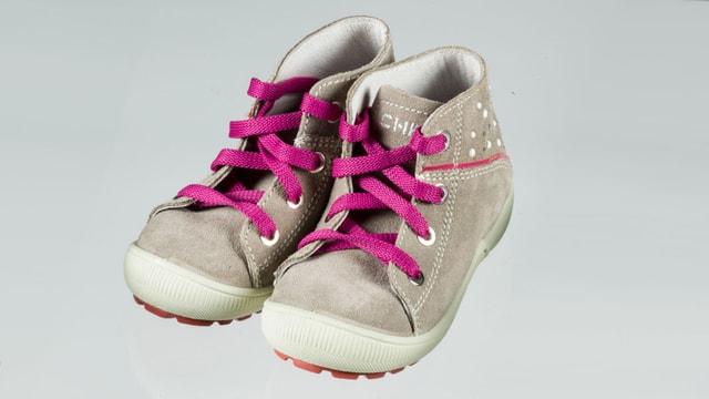 Ein paar graue Kinderschuhe mit rosa Schuhbändeln.