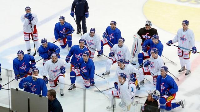 Die Spieler der Kloten Flyers hocken auf dem Eis und schauen auf eine Tafel.