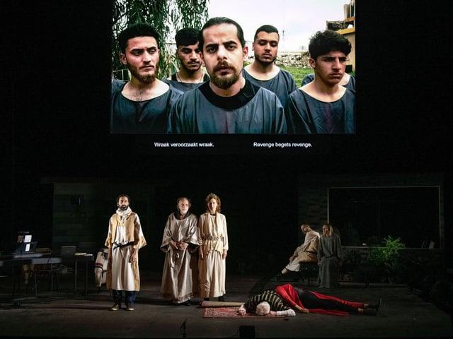 Eine Theaterbühne: Vorne sind fünf SchauspielerInnen, auf dem Bildschirm hinten sind fünf Darsteller.