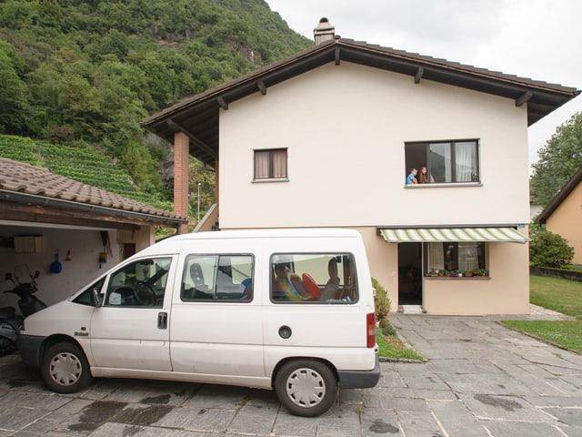 Sofia und Enea blicken aus dem Fenster im ersten Stock vom Haus der Familie Leonardi. Vor dem Haus steht das Familienauto, ein weisser Van.