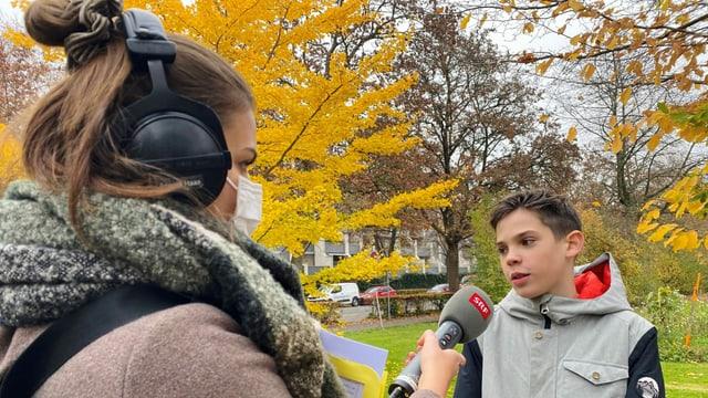 Die Radioreporterin hält ein Mikrofon, welches sie dem Jungen hinstreckt.