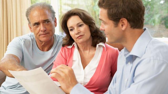 Ein Ehepaar diskutiert mit einem Mann, der ein Dokument zeigt.