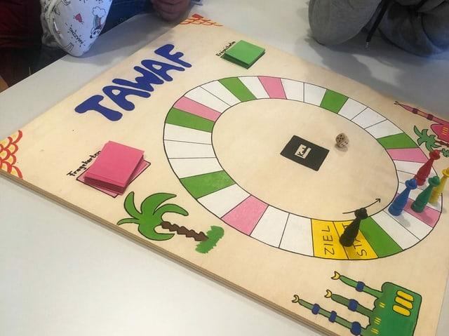 Ein quadratisches Spielbrett mit zahlreichen weissen, grünen und pinkfarbenen Feldern, die im Kreis angeordnet sind, liegt auf einem Tisch.