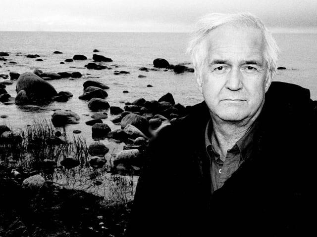 Der Autor Henning Mankell auf einem Schwarz-weiss-Bild an einer Küste.