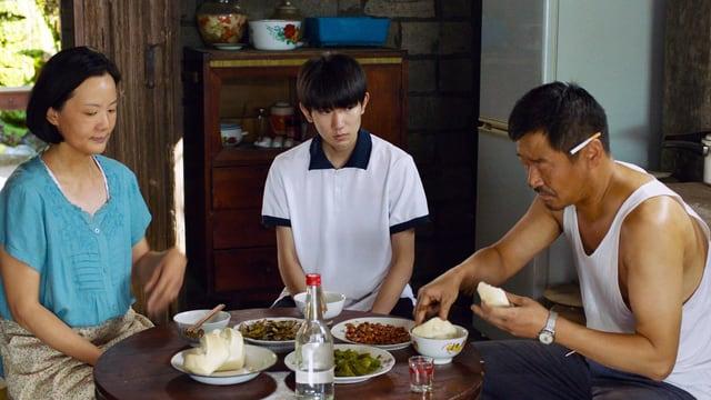 Eine Frau, ein Jugendlicher und ein Mann sitzen alle am oberen Ende eines Holztisches, der bedeckt ist mit Essen. Im Hintergrund ist ein Wohnzimmer sichtbar. Die drei personen machen einen betrübten Eindruck.