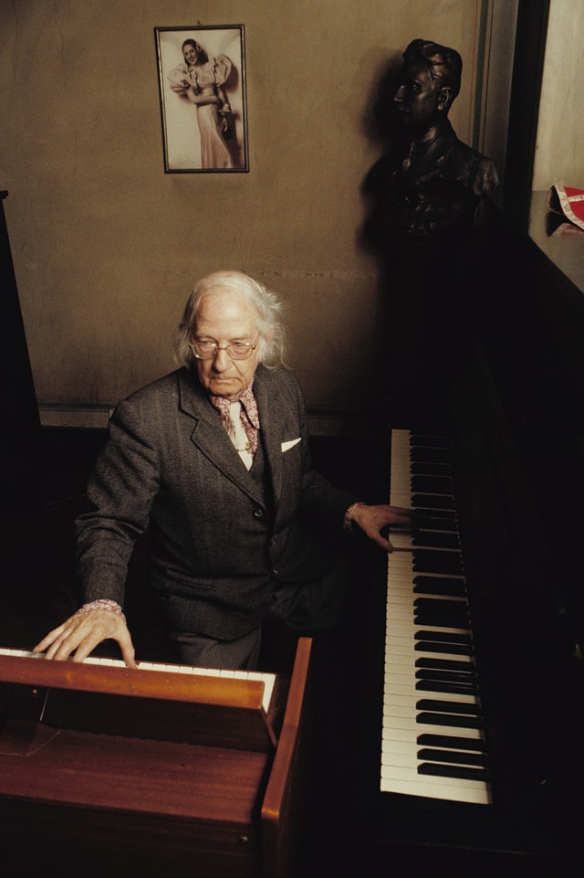 Ein Mann im Altersheim zwischen zwei Klavieren.