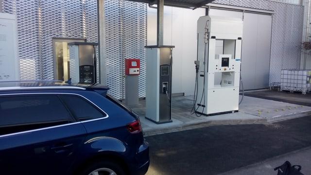 Drei moderne Zapfsäulen in einer Tankstelle, davor ein Auto