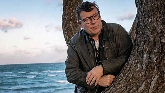 Ein Mann mit dunkelbrauer Lederjacke und Brille lehnt an einen Baum.