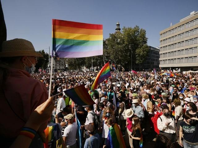 Menschen mit Regenbogenfahnen stehen auf einem Platz.