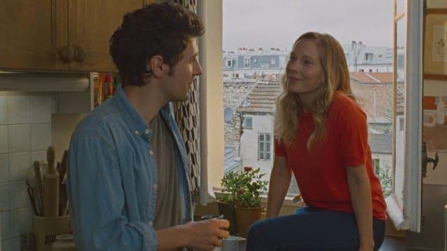 Frau mit langen , blondern Haaren sitzt auf einem Fenstersims. Neben ihr in der Küche steht ein junger Mann.