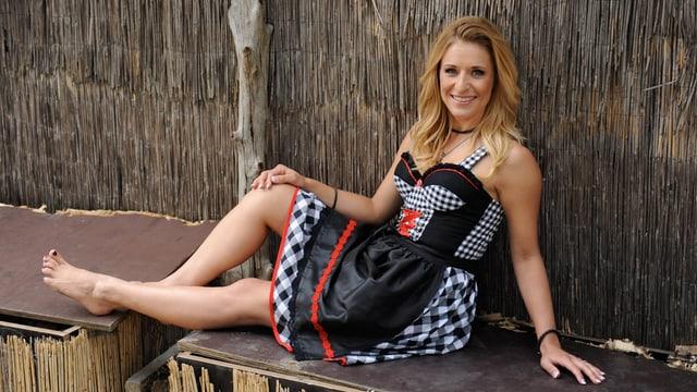 Schlagersängerin Stefanie Hertel sitzend im schwarz-weiss-roten Dirndl aus ihrer eigenen Kollektion.