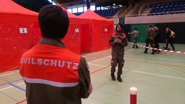 Mann mit Zivilschutz-Jacke vor Zelten