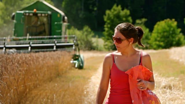 Claudia Zimmermann läuft durchs Getreidefeld. Hinter ihr fährt ein Mähdrescher.