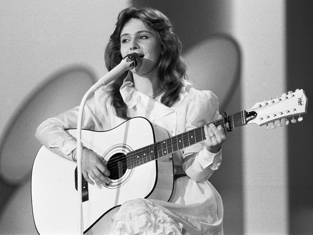 Eine junge Sängerin im weissen Kleid und mit einer weissen Gitarre.