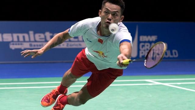 Ein Badmintonspieler hechtet nach dem Federball.