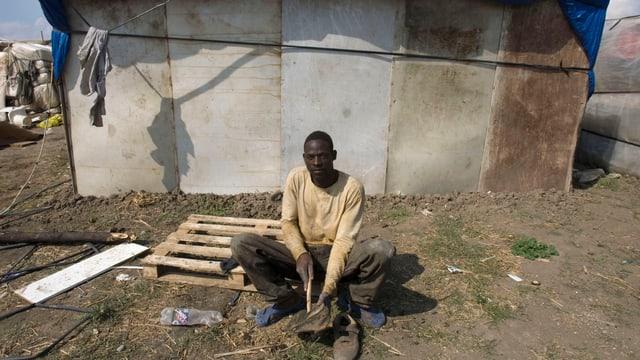 Ein afrikanischer Mann sitzt vor einer baufälligen Hütte auf einem Feld.