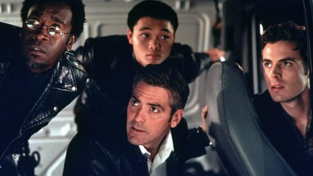 """Szene aus dem Film """"Ocean's Eleven"""": Im Inneren eines Kleinbusses, George Clooney sitzt in der Mitte, um ihn herum sind drei Männer. Alle sind in Schwarz gekleidet und schauen etwas verwirrt nach links vorne."""