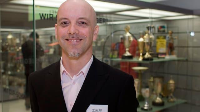 Ein lächelnder Gregor Dill steht vor zwei Gestellen mit Pokalen
