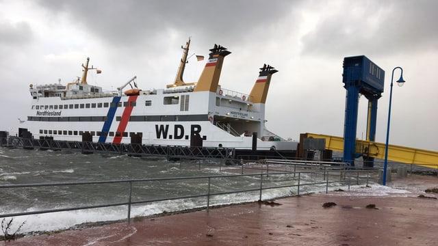Wellen schwappen über die Hafenmole in Amrum