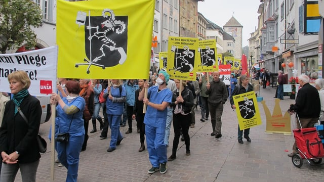 Männer und Frauen mit Plakaten an der Demonstration durch die Schaffhauser Altstadt.