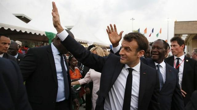 Macron winkt in Elfenbeinküste den Leuten zu.
