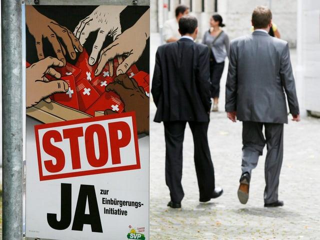 Wahlplakat, darauf: Viele Hände greifen nach Schweizerpässen. Neben Plakat laufen zwei Männer vorbei.