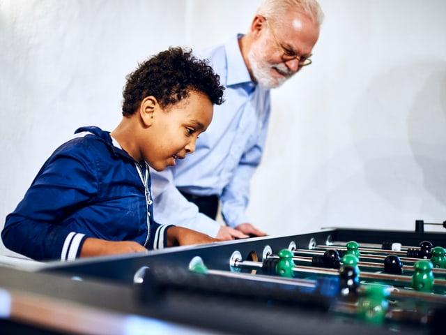 Ein dunkelhäutiger Junge spielt mit einem älteren Pfarrer Tischfussball.