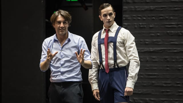 Zwei Männer stehen auf der Bühne. Der Mann rechts in kurzen Hosen, Hosenträgern und einer roten Krawatte.