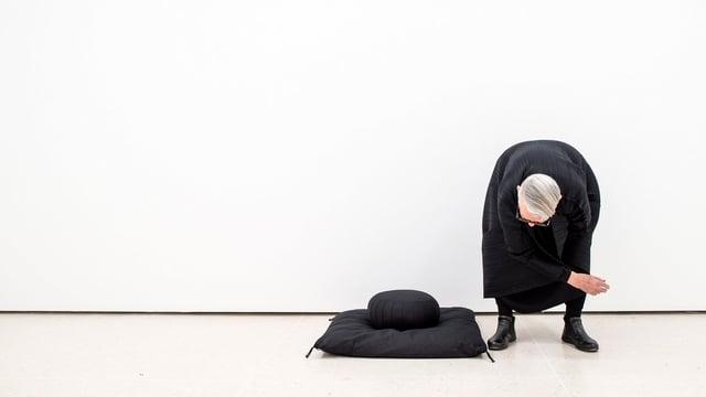 Christa de Carouge steht in einem weissen Raum und beugt sich nach vorne.