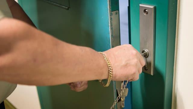 Ein Gefängniswärter schliesst eine Türe auf.