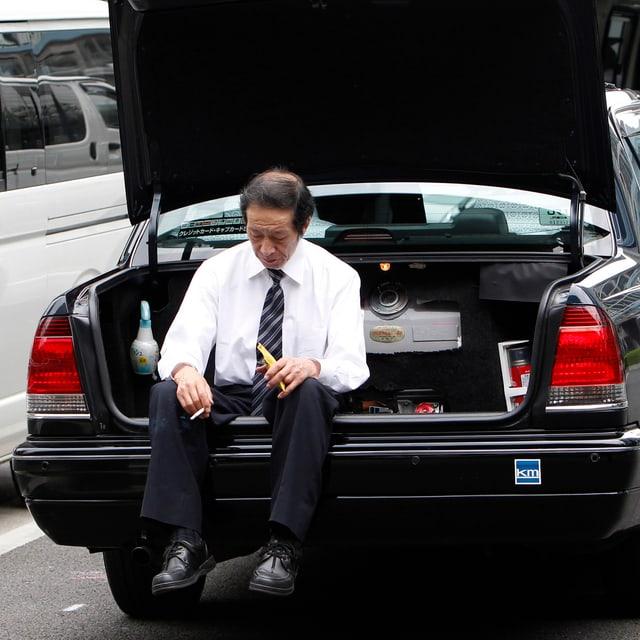 Ein Taxifahrer raucht im Kofferraum seines Autos eine Zigarette.