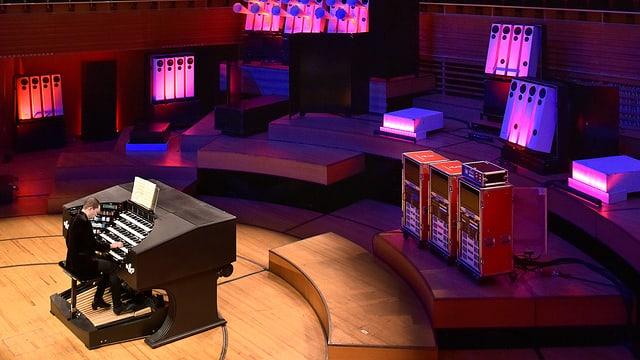 Ein Mann sitzt an einer Orgel, im Hintergrund grellpinke Lautsprecher.