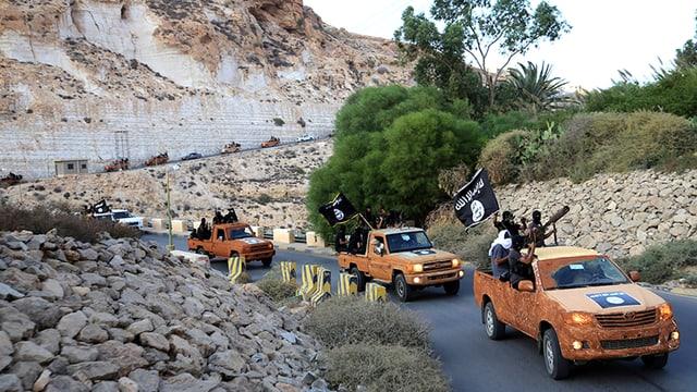 Schwarz vermummte und bewaffnete Menschen in gelben Trucks fahren auf einer Bergstrasse.