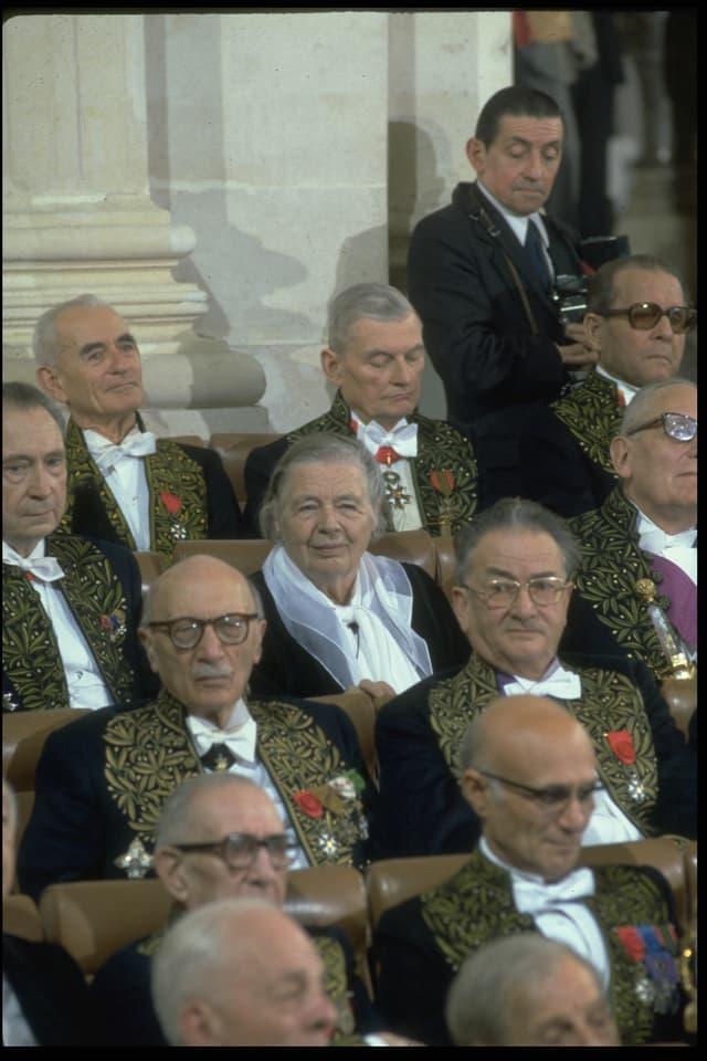 Marguerite Yourcenar sitzt in der Académie française. Sie ist umgeben von Männern.