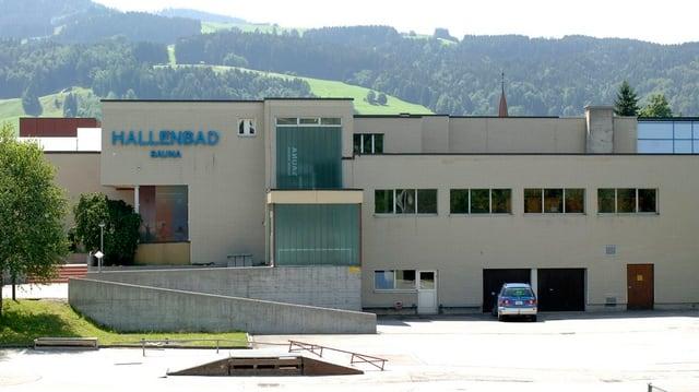 """Aussenanschicht Hallenbad. Graue Fassade, blaue Aufschrift """"Hallenbad"""""""
