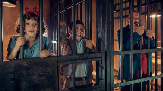 Im Gefängnis: In der linken Zelle sind ein Mädchen und ein junge eingesperrt, in der rechten ein Mann. Sie halten sich an den Gitterstäben fest und schreien.
