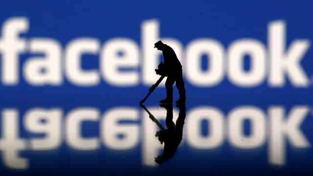 Facobook-Logo im Hintergrund, vorne die Figur eines Arbeiters mit Pressluftbohrer.
