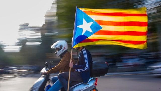 Zwei Personen auf Motorroller sitzend. Inoffizielle Flagge der katalanischen Unabhängigkeitsbewegung erkennbar