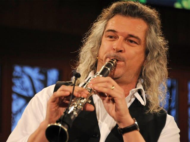 Ein Klarinettist mit schulterlangen Haaren.
