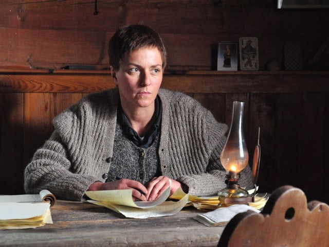 Schauspielerin Martina Gedeck sitzt in dieser Filmszene an einem Schreibtisch mit einer Öllampe.