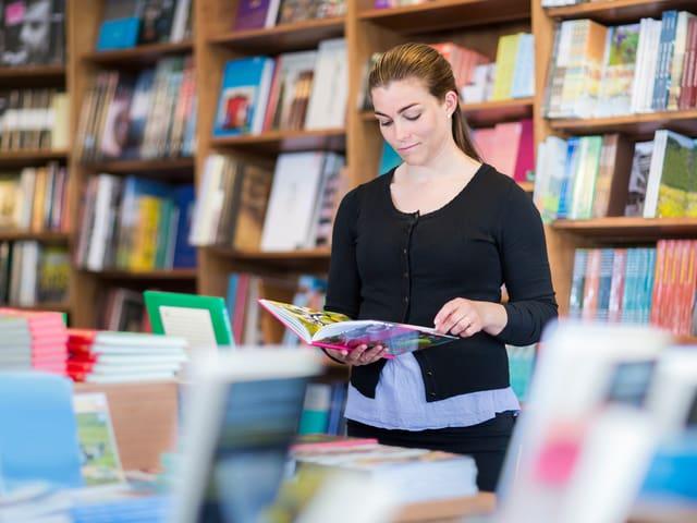 Eine Frau in einem Buchgeschäft ist in ein Buch vertieft.