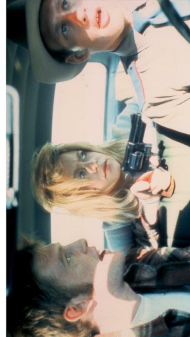 Drei Personen sind in einem Auto. Es fährt ein Polizist, auf den eine Pistole gerichtet ist.