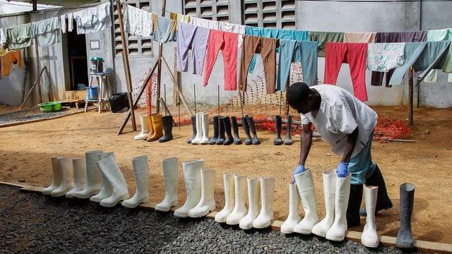 Eine liberianische Krankenschwester holt frisch desinfizierte Stiefel.