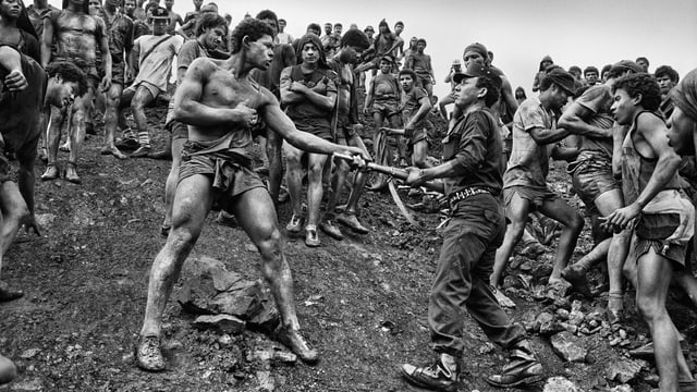 Schwarz-Weiss-Foto von zwei streitenden Arbeitern am Hang vor einer brasilianischen Goldmine.