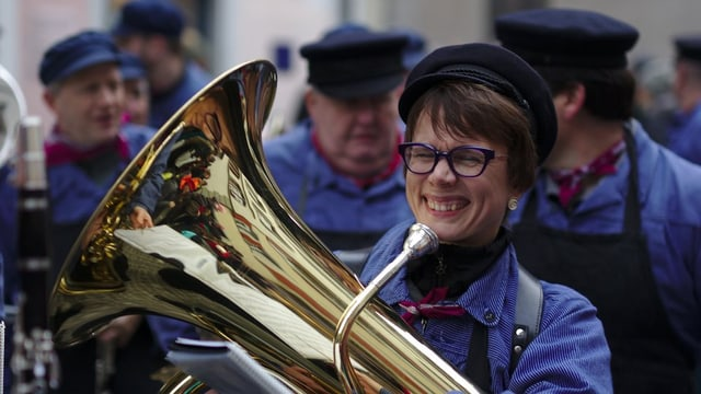 Frau mit Tuba während Marsch-Umzug.
