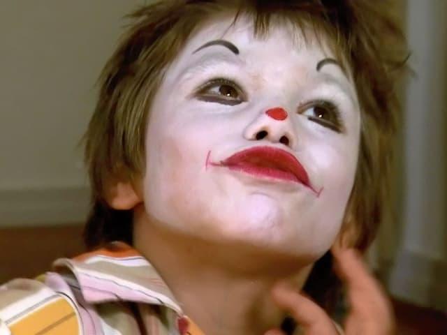 Die kleine Danja mit weiss bemaltem Gesicht und rot geschminktem Mund.