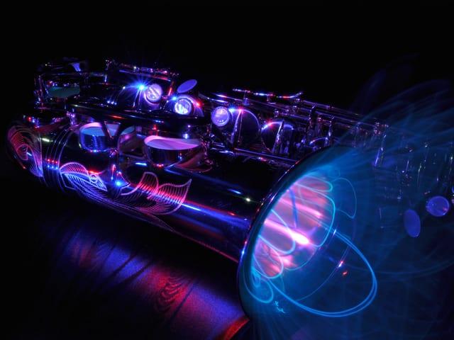 Ein Saxofon in der Dunkelheit leuchtet an verschiedenen Stellen in rosa, blauen und violetten Farben.